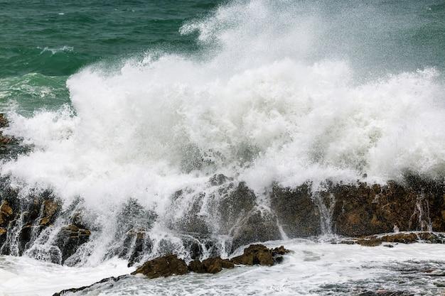 南アフリカのヘルマナスにある巨大な波が岩の多い海岸線を破壊