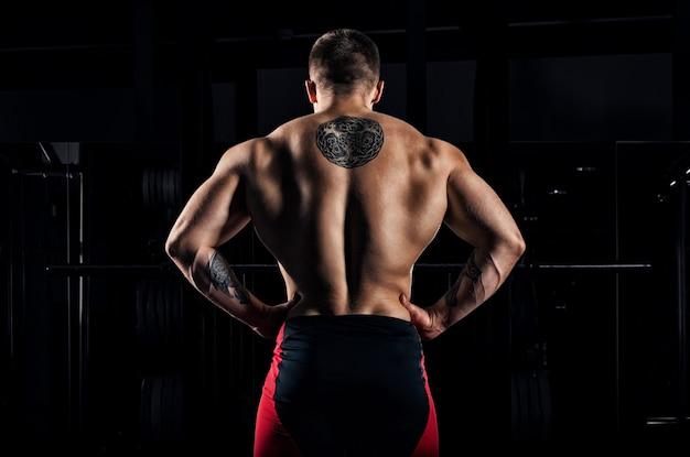 巨大な重量挙げ選手がカメラに背を向けて立ち、巨大な背中を見せています。