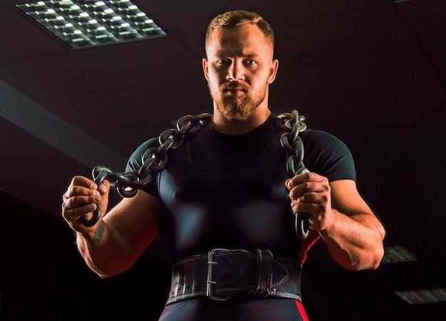 Огромный штангист с цепью на шее в спортзале