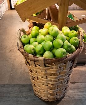 Огромная плетеная корзина свежих зеленых яблок
