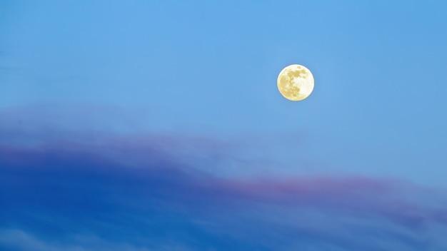 青と紫の色合いで構成される空の巨大な黄色い月