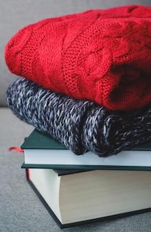 Hugge秋の冬のコンセプト、灰色の背景、寒い天候、居心地の良い家庭の赤いセーターと本