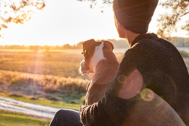 Обнимать собаку в красивой природе на закате. женщина перед вечерним солнцем сидит со своим питомцем рядом с ней и наслаждается красотой природы