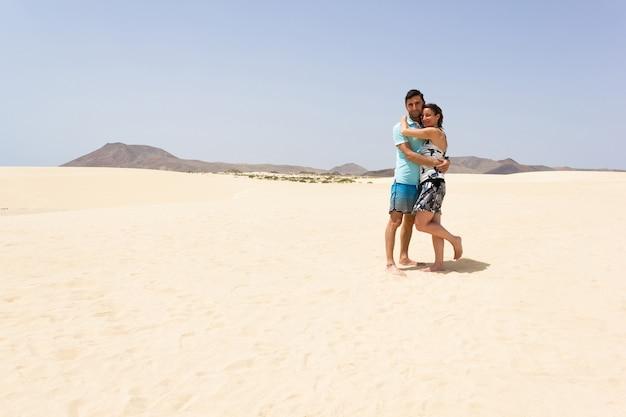 コラレホ自然公園の空の砂丘でポーズをとるハグカップル。スペイン、フェルテベントゥラ島の砂漠でポーズをとる男女。夏の観光、人気の旅行先のコンセプト