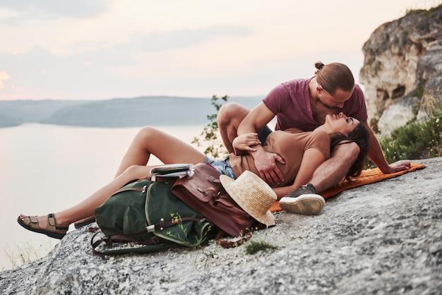 川や湖の海岸を眺めながら岩山の上に座っているバックパックとカップルを抱き締めます。自由とアクティブなライフスタイルのコンセプト