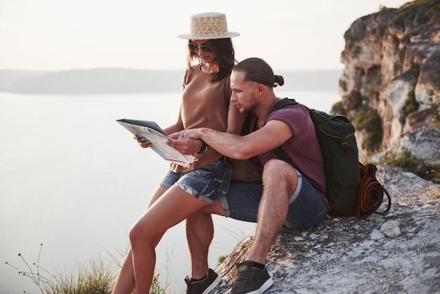 川や湖の海岸の景色を楽しみながら岩山の上に座っているバックパックとカップルを抱き締めます。山と海岸、自由とアクティブなライフスタイルのコンセプトに沿って旅行