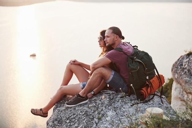 Обнимая пара с рюкзаком, сидя на вершине скалы