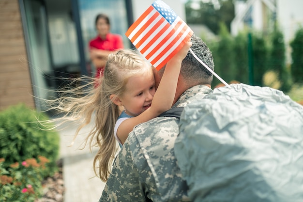 Hugging daddy tight. happy little daughter holding little american flag hugging daddy tight
