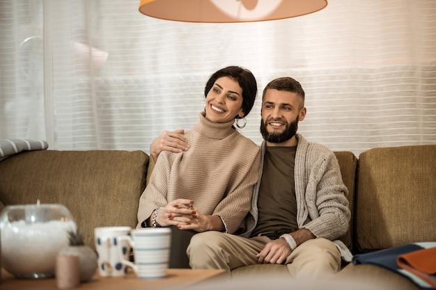 お互いを抱きしめます。居間でテレビを見ながら非常に近くに座っている黒髪のかわいいカップル