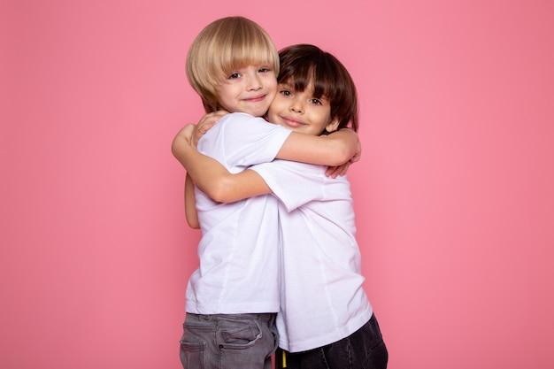 Обнимаю друзей маленький ребенок мальчики мило очаровательны на розовой стене