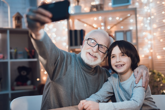 Hugging grandfather and grandson making selfie