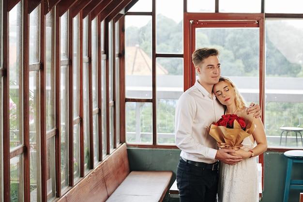 Обнимая счастливой молодой красивой пары с букетом цветов, наслаждаясь романтическими данными