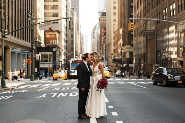 Hugging newlyweds stand in the middle of the street in new york city