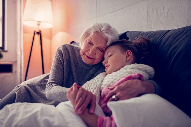 Hugging sick girl. grey-haired loving and caring granny hugging her sick cute girl falling asleep