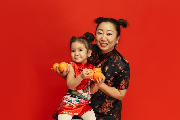 Abbracciare, sorridere, tenere in mano mandarini. . ritratto asiatico della figlia e della madre sulla parete rossa in vestiti tradizionali. celebrazione, emozioni umane, vacanze. copyspace.