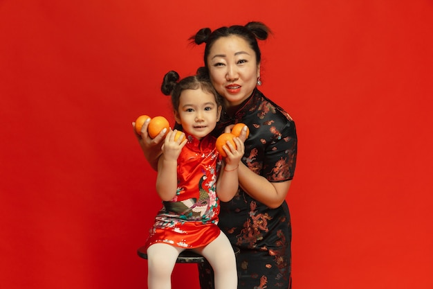 Hugging, smiling, holding mandarines. happy chinese new year 2020. asian mother and daughter portrait on red background in traditional clothing. celebration, human emotions, holidays. copyspace.