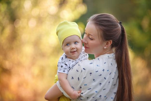 小さな子供の夏の写真撮影を抱擁、赤ちゃんの赤ちゃんはママにキス