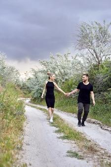茂みの枝で抱擁とキスを愛するカップル。男性が女性にキスをしている道を歩きます。愛、愛情、関係、顔の鮮やかな感情。東部の愛するカップル