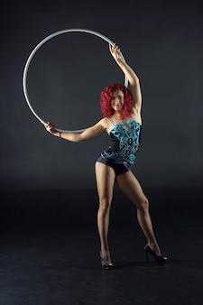 훌라후프 소녀는 예술적인 의상을 입고 서커스 공연을 합니다. 어두운 배경에서 촬영하는 스튜디오.