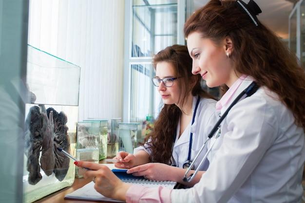 Анатомия человека. студенты-медики двух девушек изучают дыхательную систему на настоящие легкие в фармацевтике. анатомический музей. концепция санитарного просвещения