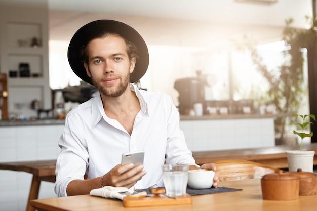 人間と現代の技術コンセプト。ランチ中に無料のワイヤレス接続を楽しんでいる彼のスマートフォンでインターネットをサーフィン、黒い帽子と白いシャツでハンサムな若い白人学生の肖像画