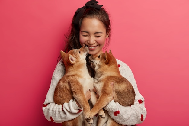 Human and animal friendship concept. cheerful girl happy to get two pedigree puppies on her birthday, kisses pet