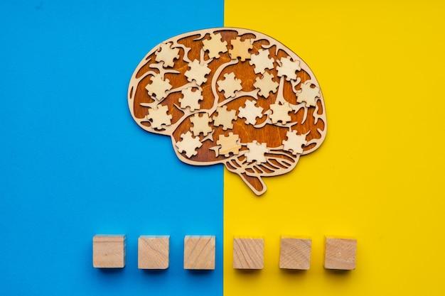 흩어져있는 퍼즐 조각과 인간의 두뇌. 글꼴에 자폐증이라는 단어를 쓸 수있는 6 개의 큐브.