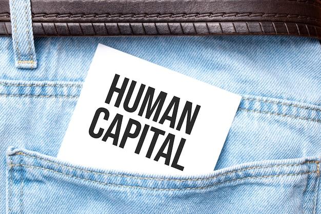 Human capital words on a white paper stuck out from jeans pocket. business concept.