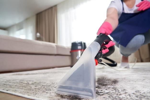 Человек чистит ковер в гостиной с помощью пылесоса дома