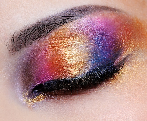 Human closed eye with multicoloured eyeshadow - macro shoot