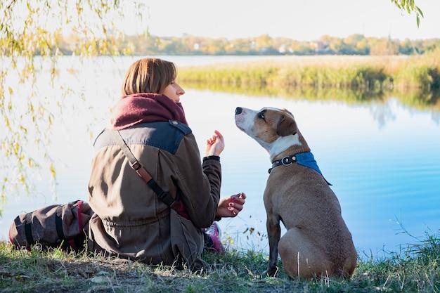 Человек общается с собакой. молодая собака сидит и слушает свою хозяйку в красивой природе возле озера.