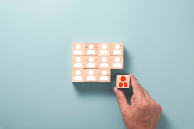 Human development and different thinking concept, hand holding wooden cube block printed screen red manager icon move out from white human icons.