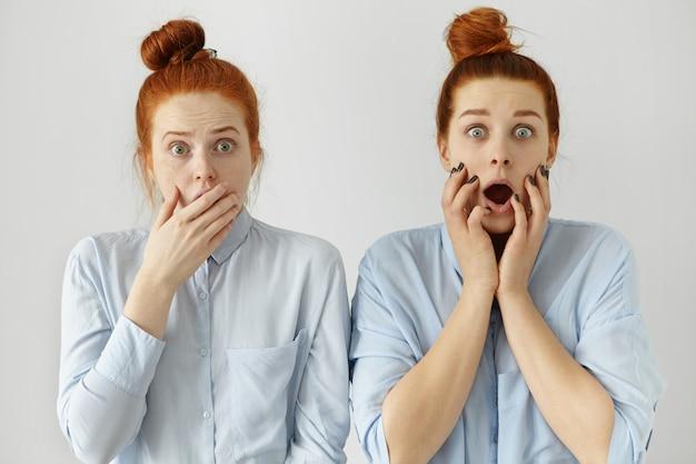 Человеческие эмоции и чувства. выражения лица. два рыжеволосых изумленных кавказских студента выглядят как близнецы с узелками волос в рубашках. глазастые сестры узнали шокирующую информацию