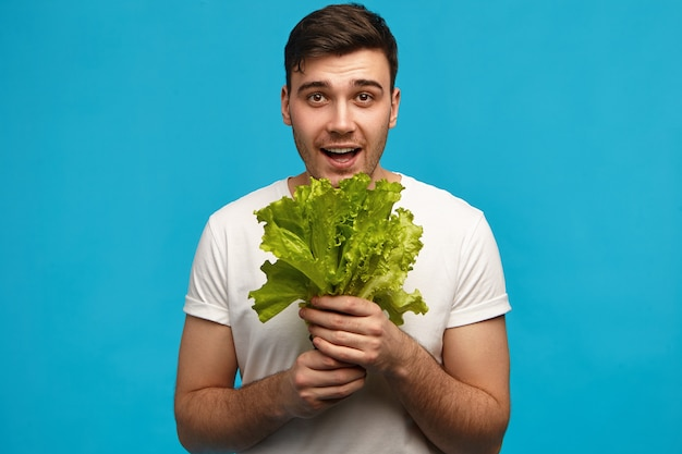 人間の感情と感情。新鮮な野菜の香りを吸い込んで、豊作に満足して、クリスピーなグリーンレタスの束を持って孤立したポーズをとっているうれしそうな若い白人の男。食品と栄養の概念