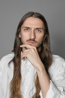 Human emotions and body language. vertical picture of stylish extraordinary male with long brown hair and mustache keeping hand on his chin