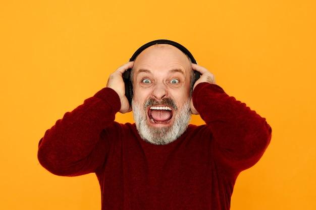 人間の感情、電子機器、最新技術のコンセプト。叫んでいるイヤホンを使用してスポーツラジオのストリームを聞いている感情的な憤慨した老人