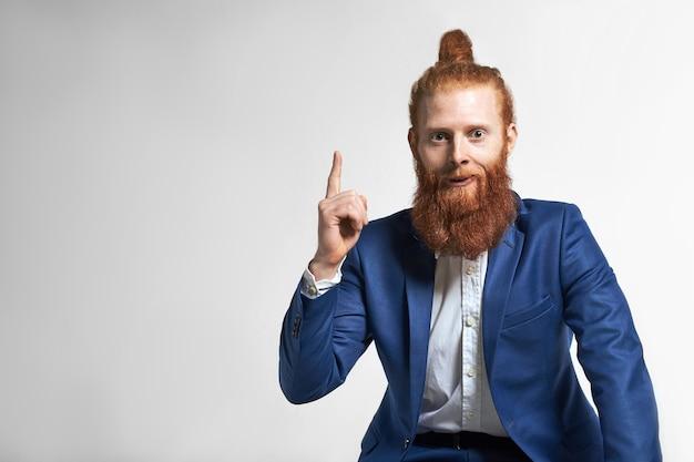 人間の感情、感情、反応。人差し指をコピースペースの壁に向けて、ファジーなひげと髪の結び目が驚きの表情をしているハンサムな感情的な若い白人男性従業員の肖像画