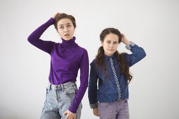 人間の感情、感情、反応、態度。白い壁に立っているスタイリッシュな服を着た2人の妹の孤立したスタジオショット