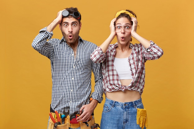 Human emotions and feelings. two surprised astonished young caucasian service technicians wearing safety eyeglasses and overalls having amazed and shocked looks, holding hands on their heads