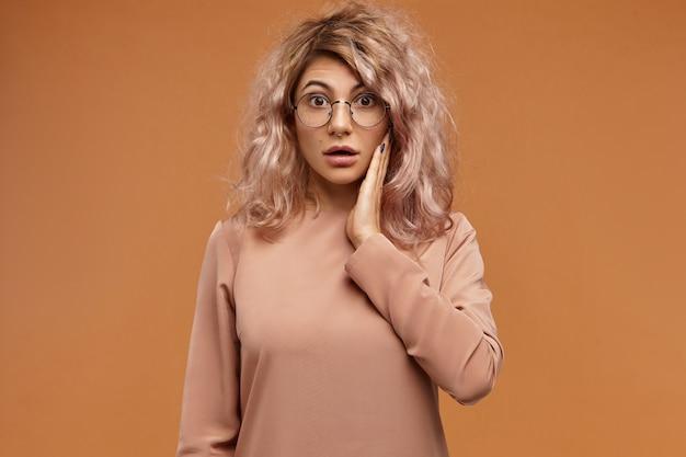 Emozioni umane, reazioni e sentimenti. colpo di ragazza emotiva divertente hipster in occhiali rotondi, con sguardo perplesso, tenendo la guancia e aprendo la bocca