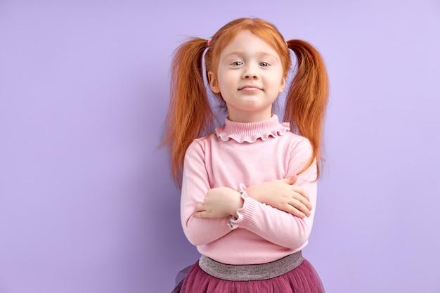 人間の感情の反応と感情の不機嫌そうな不快な顔の表情を持っている彼女の胸に腕を組んでいる少女