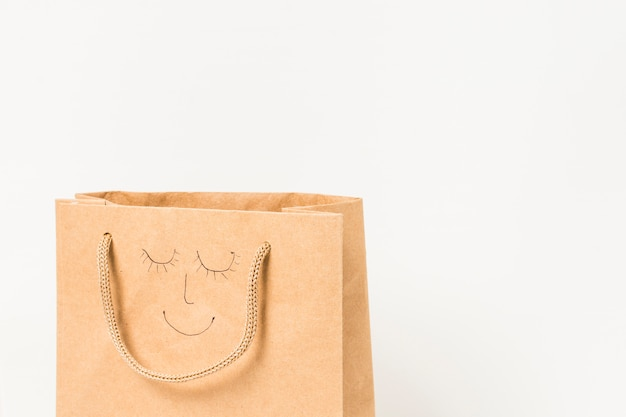 Human face drawn on brown paper bag against white surface