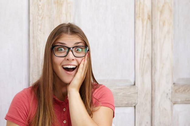 인간의 얼굴 표정과 감정. 폴로 셔츠와 그녀의 뺨에 손을 잡고 입을 넓게 여는 직사각형 안경을 쓰고 놀란 젊은 여성 직원의 초상화