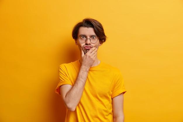 Concetto di espressioni del volto umano. l'uomo europeo adulto bello tiene le labbra imbronciate sul mento fa una smorfia divertente indossa occhiali trasparenti rotondi e maglietta casual isolata sul muro giallo.