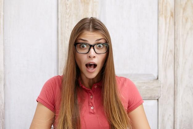 人間の顔の表情、感情、感情。何かにショックを受けて驚いた、または怖い顔をした長いストレートの髪を持つ驚いた、虫眼鏡の若い女性