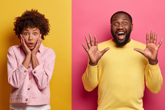 Concetto di espressioni ed emozioni del viso umano. il colpo dello studio della donna afroamericana sorpresa tiene i palmi sulle guance
