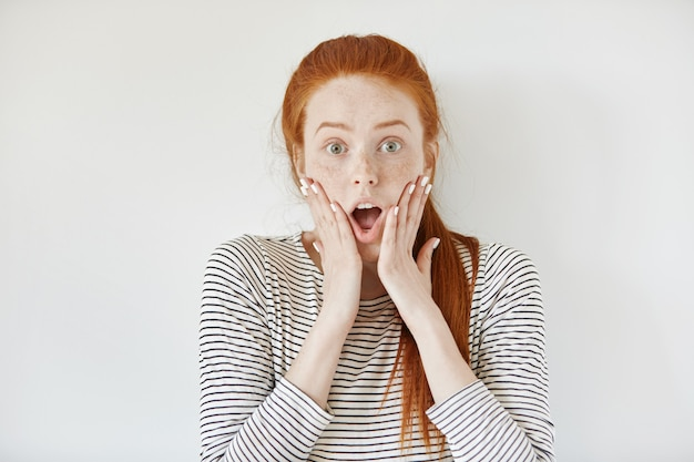 Human face expressions and emotions. redhead young female with freckles and white nails screaming with shock