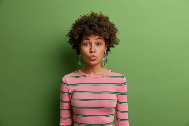 人間の顔の表情。ロマンチックな素敵な若い女性は唇を丸く保ち、ボーイフレンドからのキスを待ち、いちゃつく表情で見え、カジュアルな服を着て、緑の壁に隔離されています