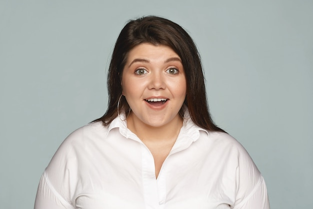 Human facial exppressions and reaction. attractive emotional young businesswoman with curvy body posing with mouth wide opened, stunned with positive news, expressing great excitement