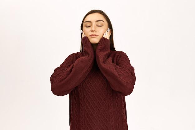 人間の表情とボディーランゲージ。目を閉じて、彼女の頬に手をつないで、夢を見て、瞑想または昼寝をして、ジャンパーを身に着けている魅力的なスタイリッシュな若いヨーロッパの女性のスタジオ画像